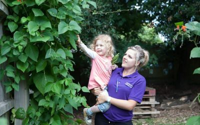 Staff and child picking runner beans at Shanklin Nursery